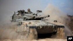 Sebuah tank Israel menuju posisi dekat perbatasan Israel-Gaza (18/7/2014). Militer Israel semakin masuk ke Gaza, Jumat, untuk menghancurkan lokasi peluncuran roket kelompok militan Hamas.