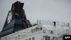 Firemen attempt to get migrants to come down from a ferry funnel on March 3, 2019 in French port of Calais, after migrants hoping to reach Britain scrambled aboard a cross-Channel ferry, sparking a vast police sweep of the ship.