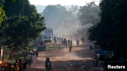 FILE - People walk on a main street in Bambari, Central African Republic, May 25, 2014.