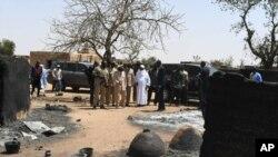 Le président du Mali, Ibrahim Boubacar Keita, examine les dégâts après l'attaque par des hommes armés à Ogossagou, au Mali, le 25 mars 2019.