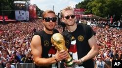 Dua pemain sepakbola nasional Jerman, Mario Goetze (kiri) dan Andre Schuerrle dalam upacara kemenangan dekat Gerbang Brandenburg Gate, Berlin, Juli 2014.