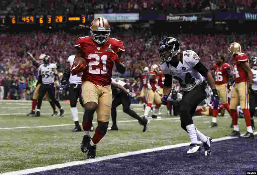 San Francisco 49ers running back Frank Gore (21) scores a third quarter touchdown against Baltimore Ravens cornerback Corey Graham (24) in the NFL Super Bowl XLVII football game in New Orleans, Louisiana, February 3, 2013.