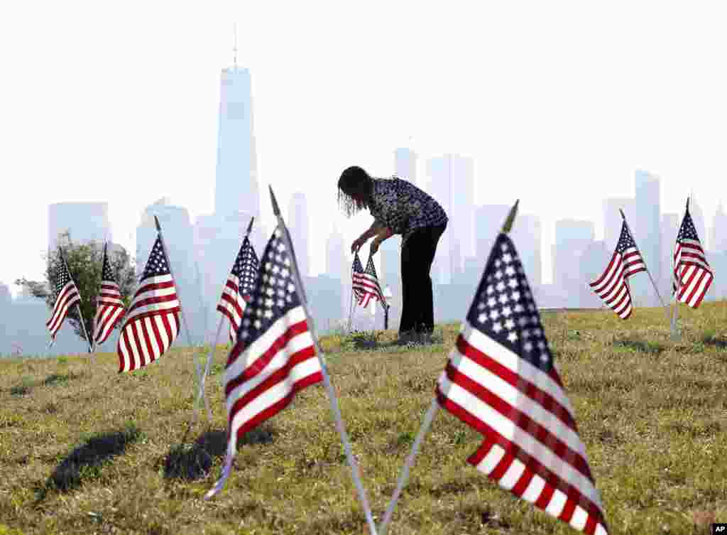 Yalenny Vargas arranges flags for the Fourth of July celebrations at Liberty State Parkin Jersey City, New Jersey.