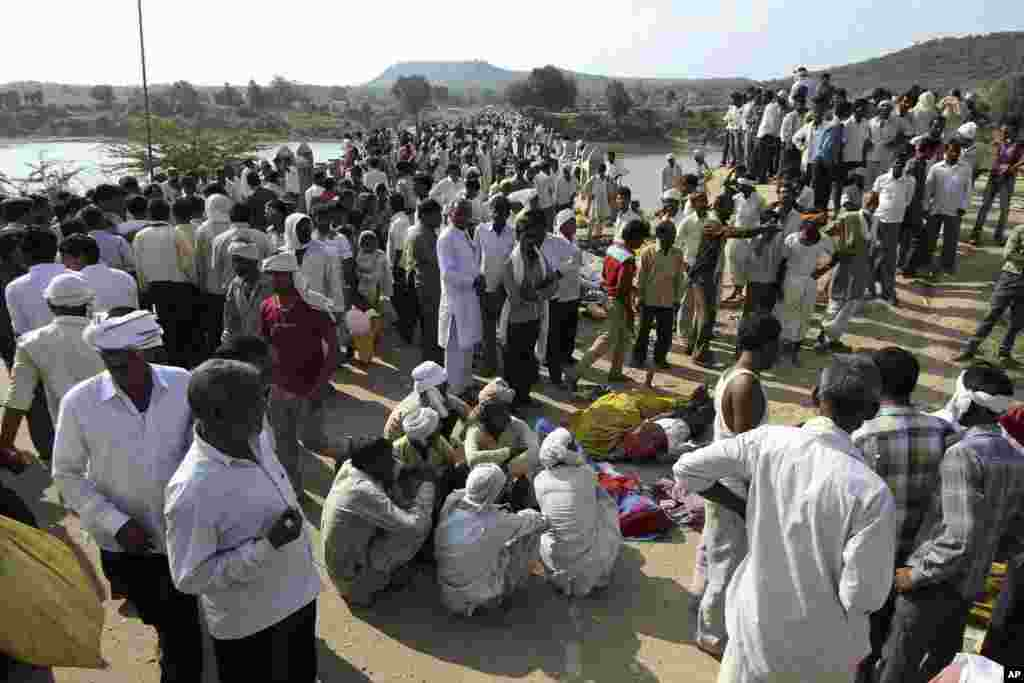 Villagers gather after a deadly stampede on a bridge across the Sindh River in Datia district in Madhya Pradesh state, India, Oct. 13, 2013.