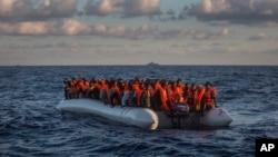 Pengungsi dan kaum migran dari kawasan sub-Sahara dalam perahu yang kelebihan muatan menunggu untuk diselamatkan oleh LSM Spanyol, Proactiva Open Arms (19/7). Utara Sabratha, dekat Libya. (foto: AP Photo/Santi Palacios)