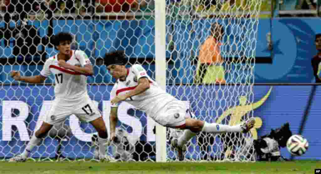 Costa Rica's Christian Bolanos kicks the ball in defense next to Costa Rica's Yeltsin Tejeda (17) during the World Cup quarterfinal soccer match between the Netherlands and Costa Rica at the Arena Fonte Nova in Salvador, Brazil, Saturday, July 5, 2014. (A