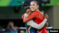 Simone Biles (L) and Aly Raisman celebrate winning gold and silver respectively at the women's individual all-around final in Rio de Janeiro, Brazil, Aug. 11, 2016.