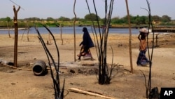 FILE - Chadian women walk past destroyed homes, in the Lake Chad shore village of N'Gouboua, March 5, 2015, following a scorched-earth attack by Boko Haram militants.