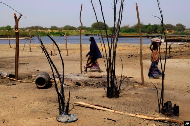 FILE - Chadian women walk past destroyed homes in the Lake Chad shore village of N'Gouboua, March 5, 2015, following a scorched-earth attack by Boko Haram militants.