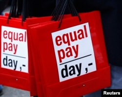 FILE - People carry bags reading 'equal pay day' in Bern, Switzerland, March 7, 2015.