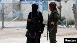 یک نگهبان کرد عضو نیروهای دموکراتیک سوریه در کنار زن یک شبه نظامی داعشی که هر دو در سوریه بازداشت شده اند - آرشیو