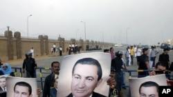 埃及穆巴拉克的支持者星期一在開羅的一家法庭外舉起穆巴拉克的畫像