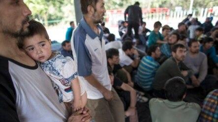 在泰国-马来西亚边界被拘留的一个疑似来自新疆的维吾尔人抱着孩子在临时收容所里(2014年3月14日)