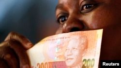 A shopper shows off South Africa's new banknotes, which features an image of former president Nelson Mandela on the front, (File photo).