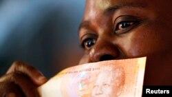 南非民众展示印有曼德拉肖像的南非新货币