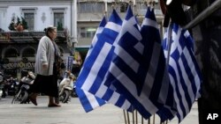 A woman walk past Greek flags for sale in central Athens, Greece as it runs perilously short of cash amid an impasse in bailout talks with its international creditors, April 22, 2015.