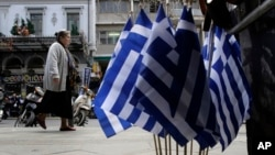 FILE - A woman walk past Greek flags for sale in central Athens, Greece as it runs perilously short of cash amid an impasse in bailout talks with its international creditors, April 22, 2015.