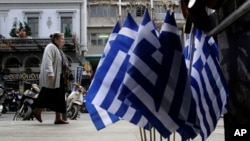 A woman walks past Greek flags that are for sale, in central Athens, April 22, 2015.