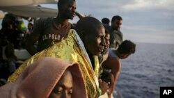 Les migrants regardent depuis le pont du bateau de l'ONG espagnole ProActiva Open Arms en attendant d'atteindre la côte italienne un jour après avoir été secourus au large de la côte libyenne, le 7 septembre 2017.