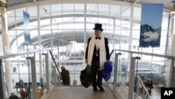 A passenger in evening dress hurries as he goes to check in for the MS Balmoral Titanic memorial cruise in Southampton, England, Sunday, April 8, 2012.