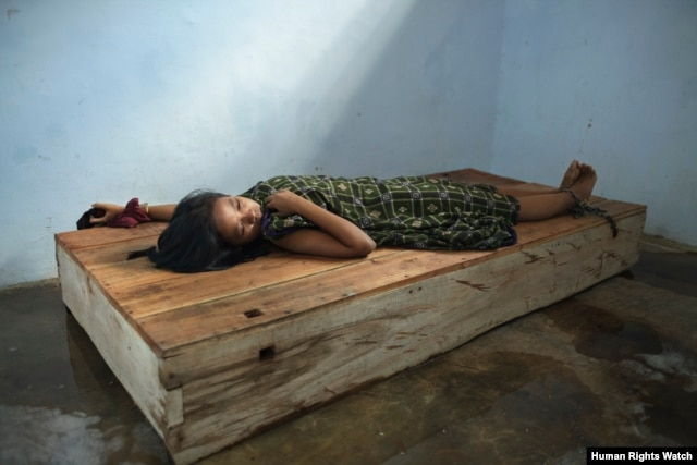 A 24-year-old female resident lies with her wrist and ankle chained to a platform bed at Bina Lestari healing center in Brebes, Central Java. © 2012 Andrea Star Reese for Human Rights Watch