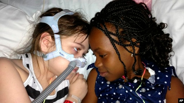 Sarah Murnaghan, left, lies in her hospital bed next to adopted sister Ella on the 100th day of her stay in Children's Hospital of Philadelphia, (File photo).