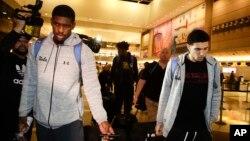 Los basquetbolistas de UCLA Cody Riley (izquierda), LiAngelo Ball (derecha) y Jalen Hill (centro atrás), son rodeados por la prensa a su llegada al Aeropuerto Internacional de Los Angeles el martes, 14 de noviembre de 2017.
