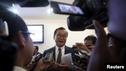 Sam Rainsy (C), president of the Cambodia National Rescue Party (CNRP), speaks to media after a plenary session at the National Assembly in Phnom Penh, March 19, 2015.