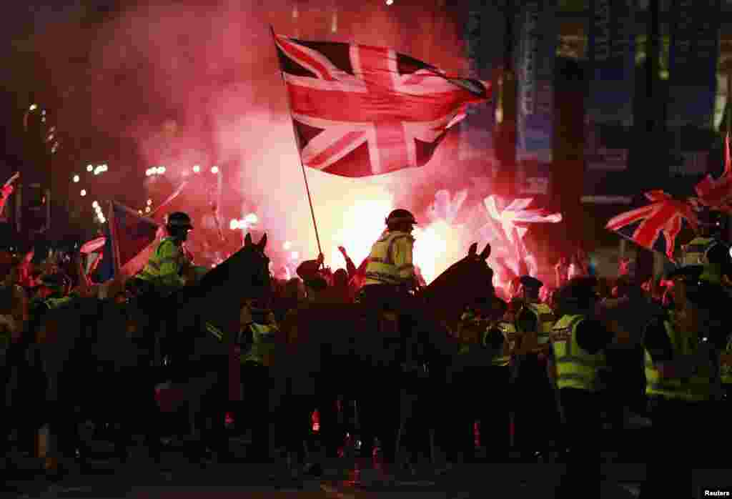 Flares are let off as police stand guard while pro-union protestors clash with pro-independence protestors during a demonstration at George Square in Glasgow, Scotland, Sept. 19, 2014.