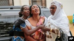 Relatives and friends grieve during the funeral of Patrick Ndikumana, Friday, July 3, 2015, in Bujumbura, Burundi. According to relatives Ndikumana was killed in the police attack in Jabe neighborhood last week. A U.N. observer mission concluded Thursday