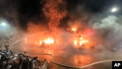 In this image taken from video by Taiwan's EBC, firefighters battle a blaze at a building in Kaohsiung, in southern Taiwan, Oct. 14, 2021.