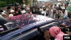 Para pendukung Malik Ishaq mengerumuni mobil yang membawa tokoh laskar-e-Jhangvi Muslim Sunni pasca-dibebaskan dari penjara Lahore (14/7). Malik Ishaq ditangkap kembali September lalu.