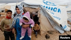 Syrian refugees leave their tents after heavy rain, Al-Zaatari refugee camp, Mafraq, Jordan, Jan. 8, 2013.