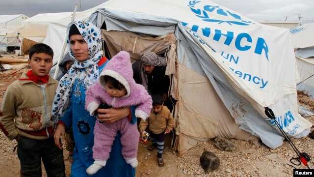 Syrian refugees leave their tents after heavy rain, Al-Zaatari refugee camp, Mafraq, Jordan, Jan. 8, 2013.