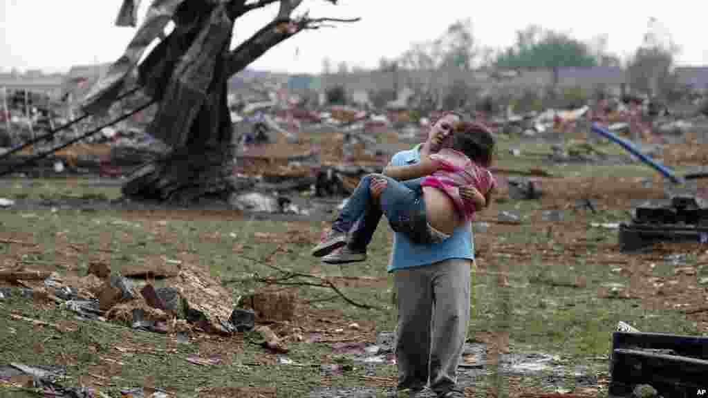 A woman carries her child through a field near the collapsed Plaza Towers Elementary School in Moore, Oklahoma, May 20, 2013.