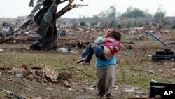 ແມ່ຍິງຜູ້ນຶ່ງກໍາລັງອູ້ມລູກຂອງລາວ ຜ່ານຊາກຫັກພັງຂອງໂຮງຮຽນ ທີ່ຖືກພາຍຸ Tornado ທໍາລາຍ, ວັນທີ 20 ພຶດສະພາ 2013.