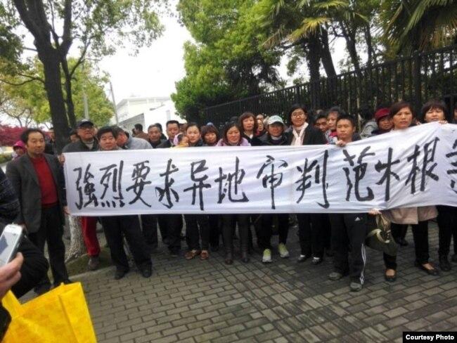 律师王宇和活动人士拉横幅要求异地审判范木根。(照片来源:现场活动人士)