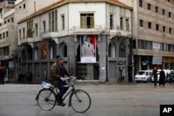 A man rides his bicycle past by a banner showing Syrian President Bashar Assad, at the clock square in the old city of Homs, Syria, Jan. 17, 2018.