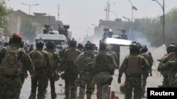 Members of the Iraqi security forces clash with protesters during a demonstration in Nasiriyah city, 375 km (233 miles) south of Baghdad, Aug. 31, 2013.