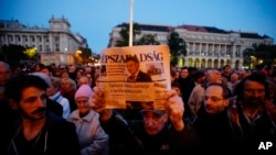 FILE - A man holds up the last printed edition of Nepszabadsag during a demonstration organized to express solidarity with the Hungarian political daily Nepszabadsag in Budapest, Hungary, Oct. 8, 2016. Mediaworks, the paper's new owner suspended 70-80 of its staffers and then dismissed most of them, bringing in pro-government editors.