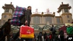 2018年2月9日,一名妇女在北京火车站外携带行李箱。中国国家统计局将此次制造业采购经理人指数下降归因于春节假期外出务工人员返乡。