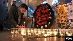 Seorang warga Moskow menyalakan lilin di St. Petersburg untuk menghormati korban tewas dalam pemboman bandara Domodedovo.