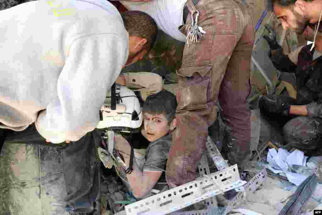 Para relawan Suriah menolong seorang anak yang terjepit di antara reruntuhan bangunan pasca serangan udara di distrik Tariq al-Bab, kota Aleppo, Suriah.