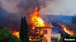 Sebuah rumah terbakar akibat lahar dari letusan gunung berapi di taman nasional Cumbre Vieja, Los Llanos de Aridane, Pulau Canary La Palma, 20 September 2021. (REUTERS/Borja Suarez)