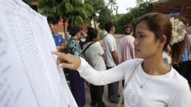A woman finds her name on a list during a local commune election in Phnom Penh, June 3, 2012.
