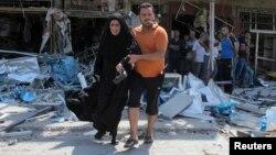 Un hombre ayuda a una mujer tras un ataque explosivo reciente en Irak.