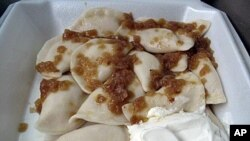 A to-go serving from St. John's Baptist Ukrainian Church includes a dozen pierogies tossed in melted butter, topped with caramelized onions and served with a generous dollop of sour cream.
