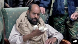 Video image made available Nov. 22, 2011 shows Moammar Gadhafi's son Seif al-Islam examining his injured hand shortly after his capture on November 19, 2011, at a safe house in the town of Zintan