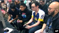 In this Aug. 25, 2017, photo, Connor Nguyen, at right, and Griffin Williams, second from right, compete in 'Super Smash Bros. Melee' at the Shine eSports event at the Seaport World Trade Center in Boston, Massachusetts. (AP Photo/Collin Bi