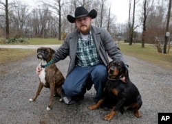 Shane Johnson poses with his dogs outside his home in Tippecanoe, Indiana, Jan. 12, 2017. Johnson was born into extremism. He eventually joined a skinhead group in addition to the KKK but finally decided to quit after getting arrested, stopping drinking and meeting the woman who is now his wife. Leaving was a real fight, though, as even relatives jumped him at a gas station one night after learning he wanted to quit.